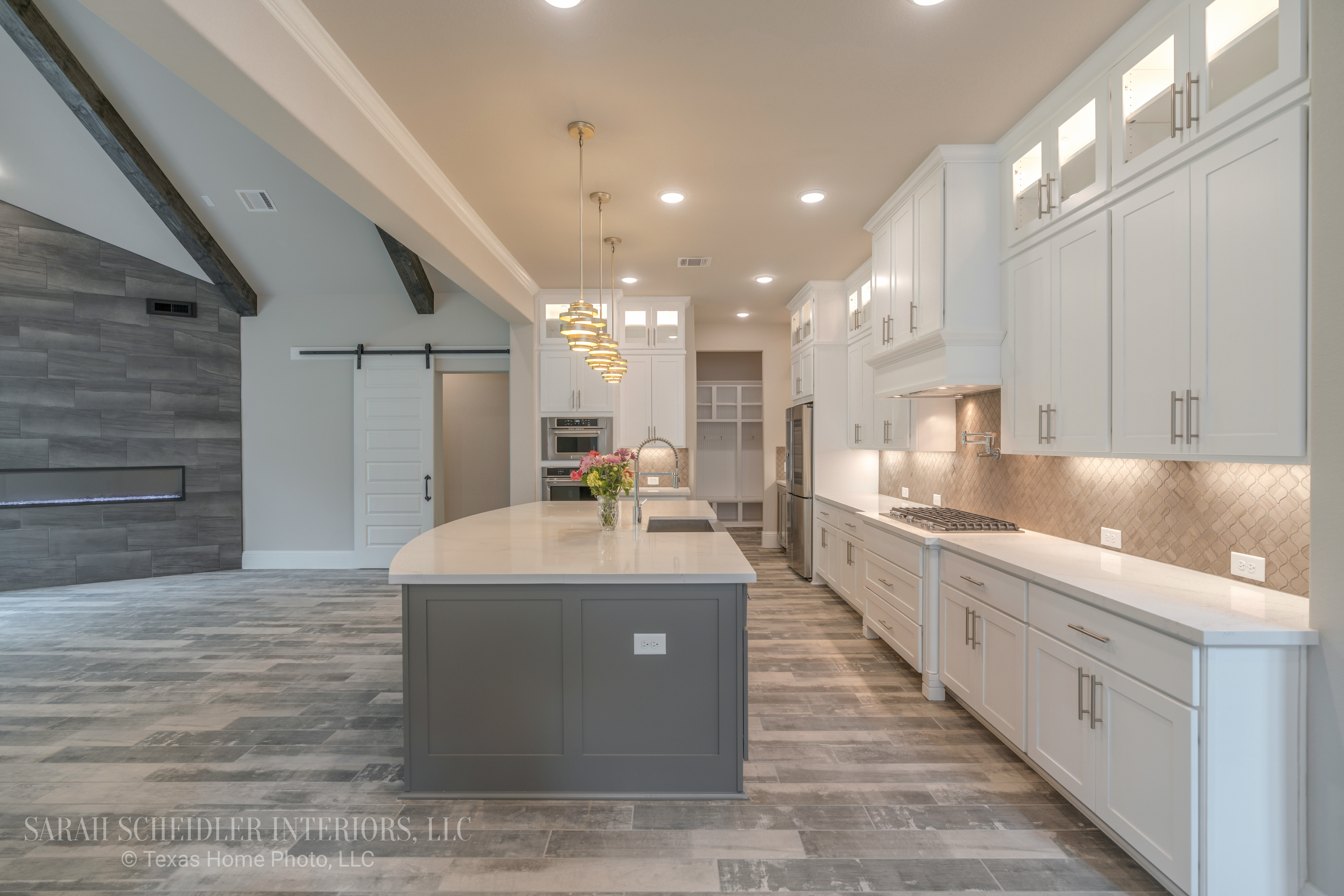 White and Grey Open-Concept Kitchen and Living Room with Floor to Ceiling Accent Tile Wall, Barn Door, and Dark Wood Beams