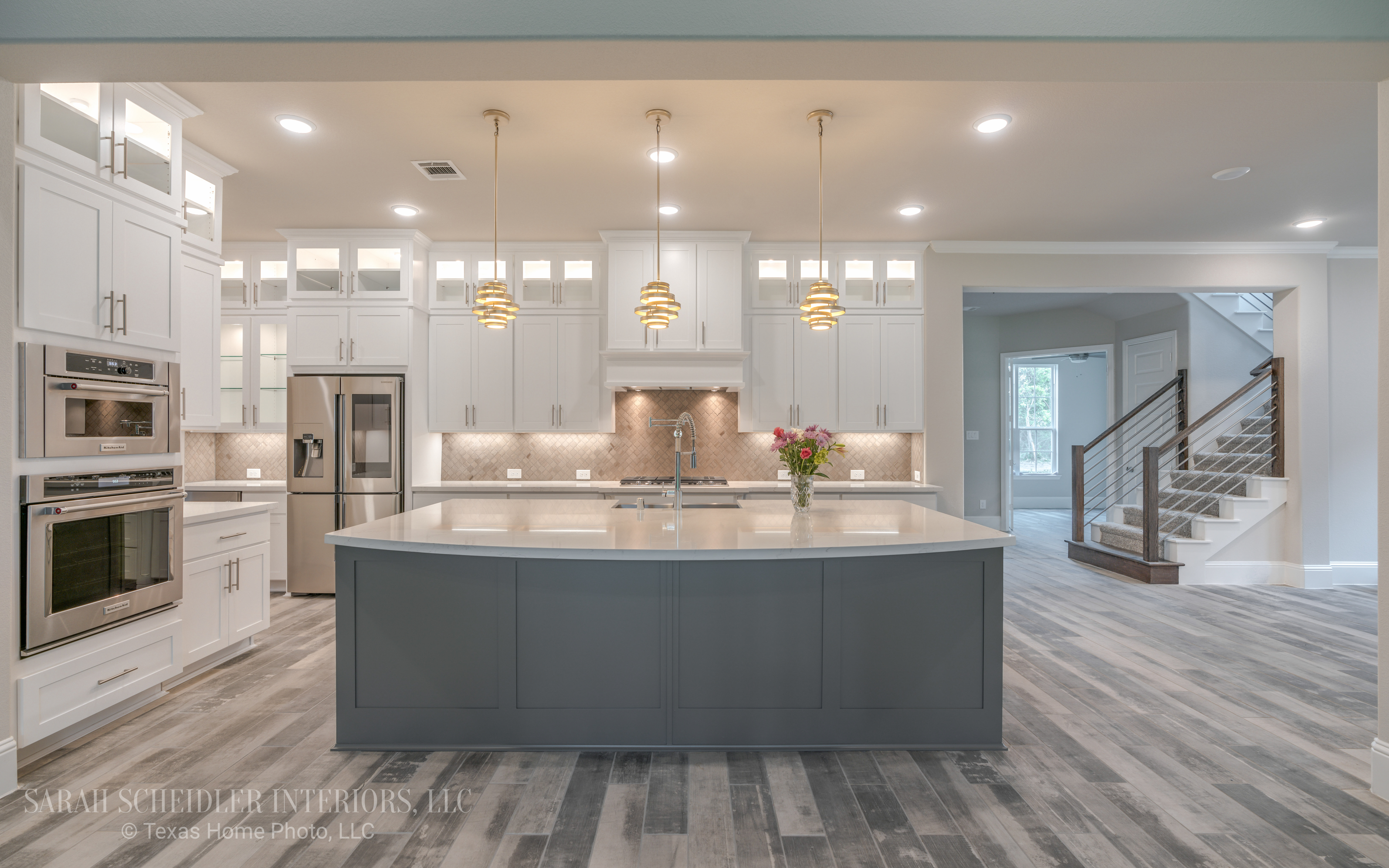 White and Grey Open-Concept Kitchen with White Kitchen Cabinets, Grey Island, Silestone Quartz Countertops, Chrome Finishes, Modern Pendants, Wood Tile Flooring