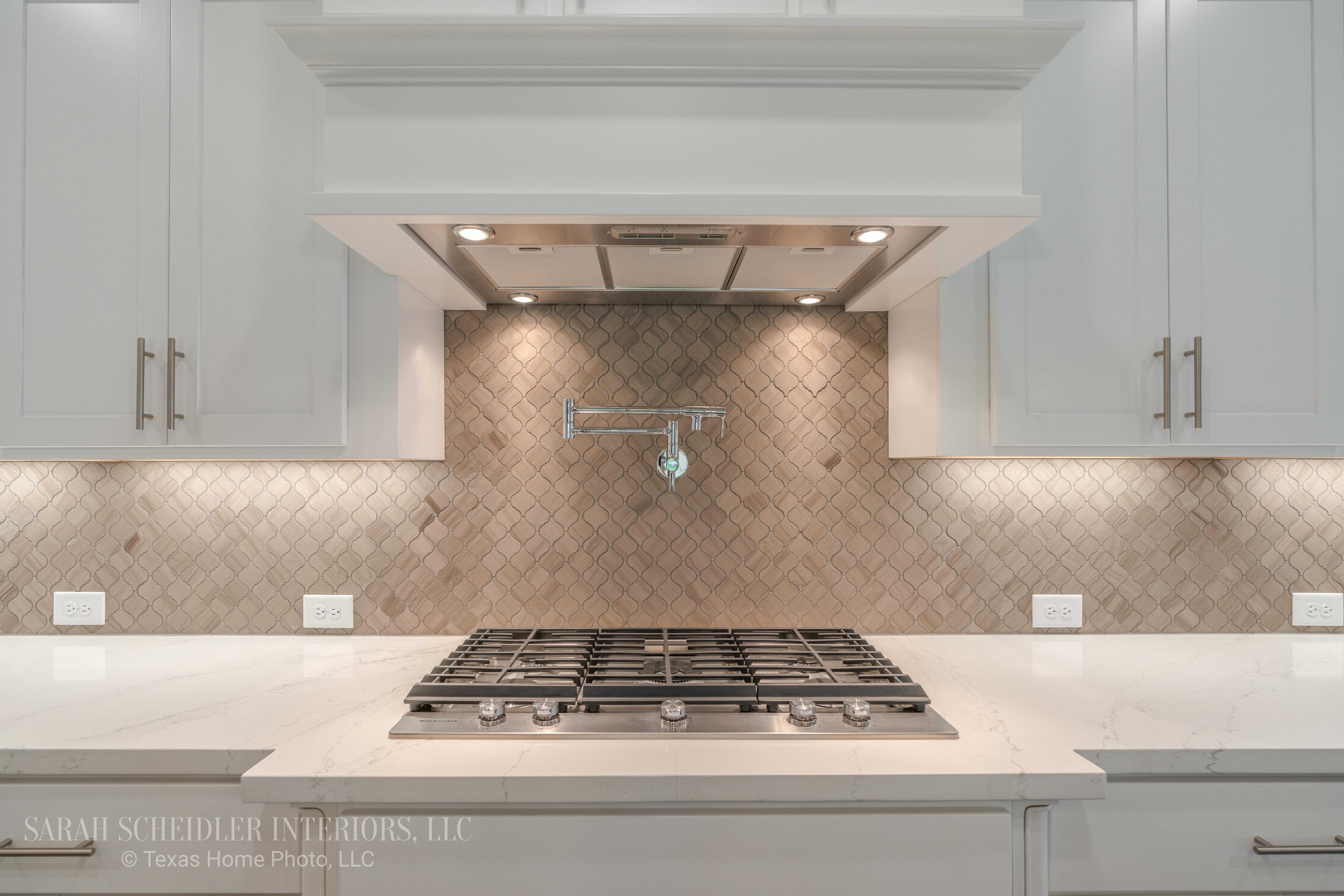 White Kitchen with Quatrefoil Backsplash, Silestone Quartz Countertops, and Chrome Finishes
