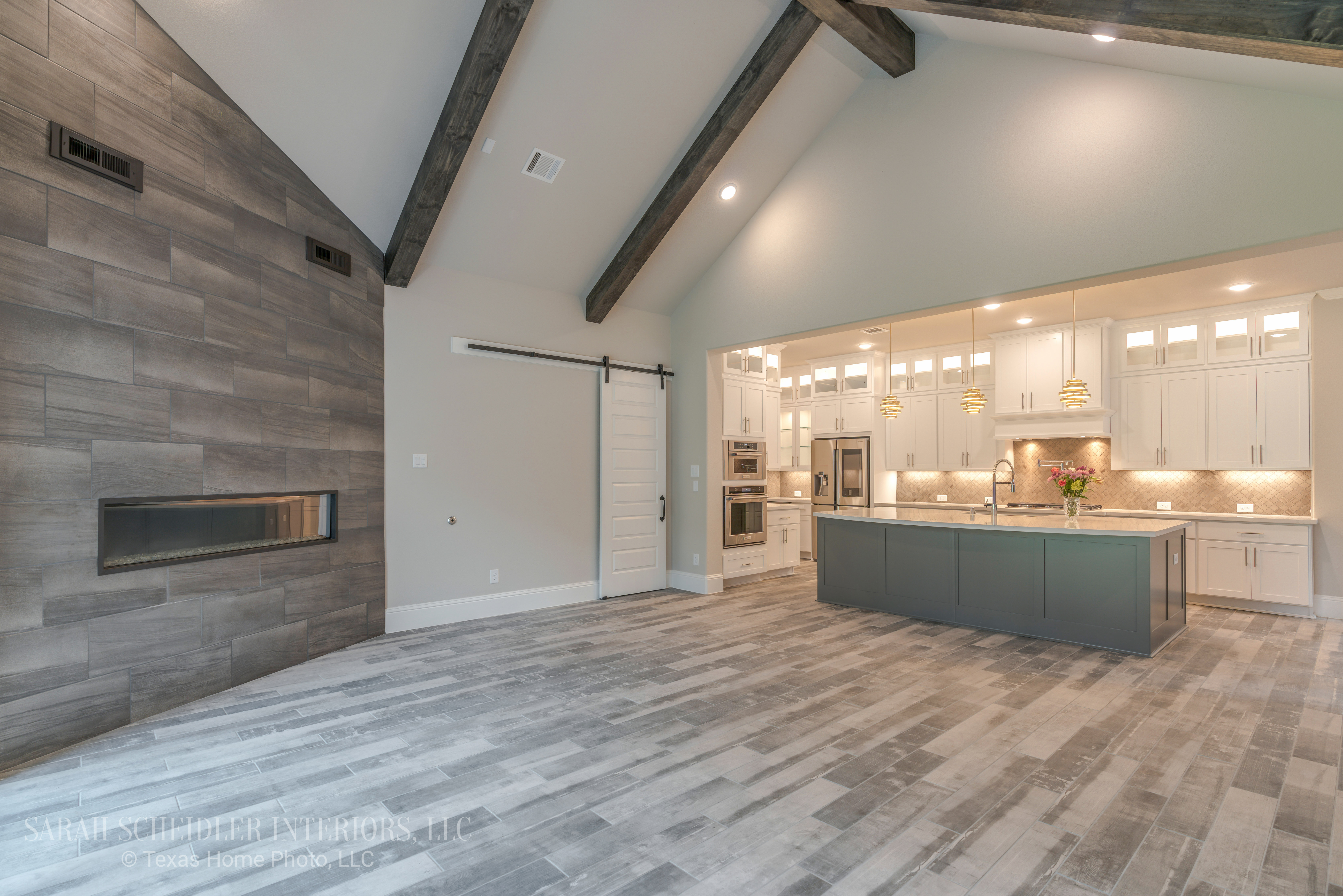 Rustic Glam Open-Concept Living Room and Kitchen with White Cabinets, Grey Island, Modern Pendant Lighting, Barn Door, Wood-Beam Ceiling, and Fireplace Wall