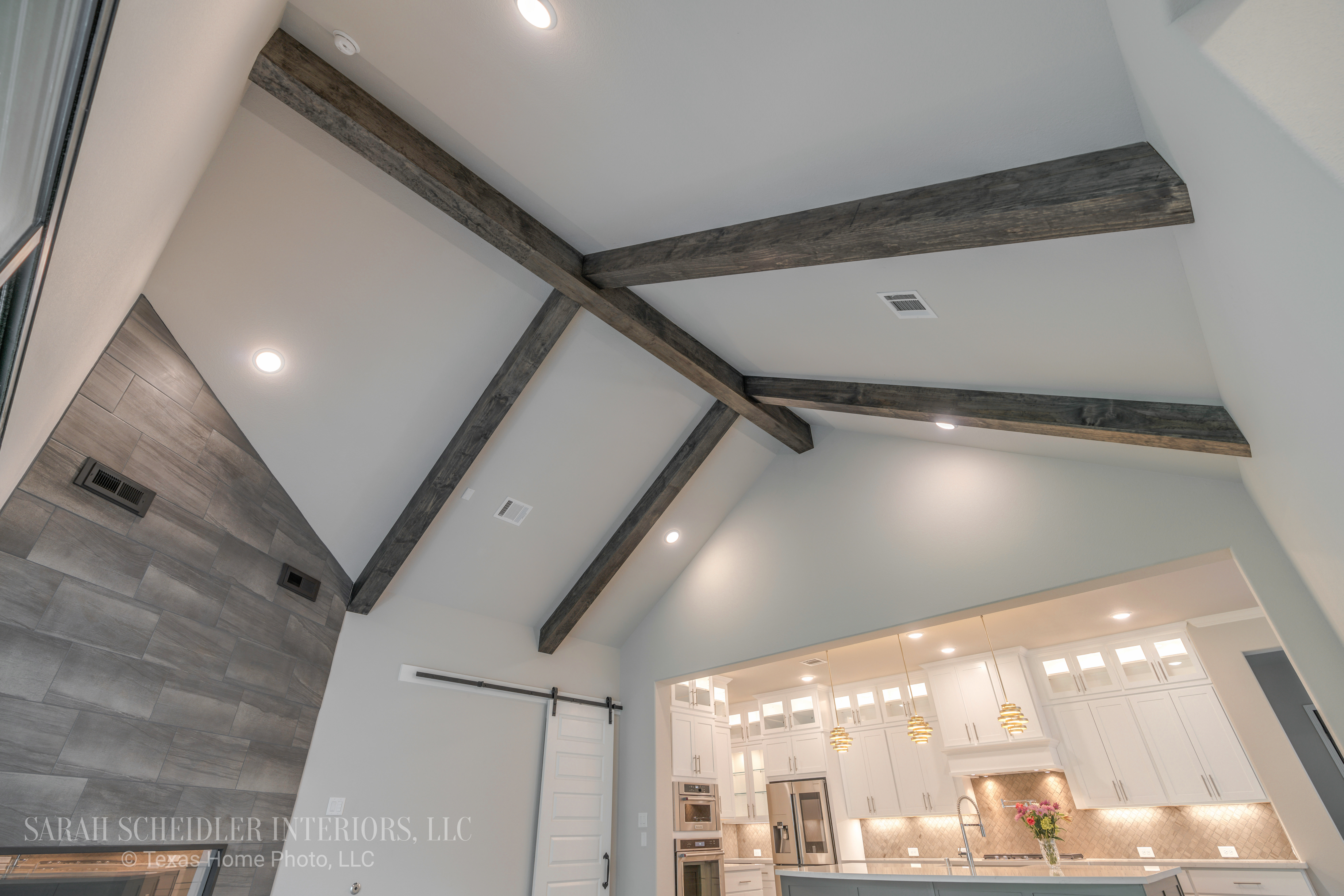 Open-Concept Living Room with Wood Ceiling Beams, Barn Door, and Fireplace Wall Looking into White and Grey Kitchen