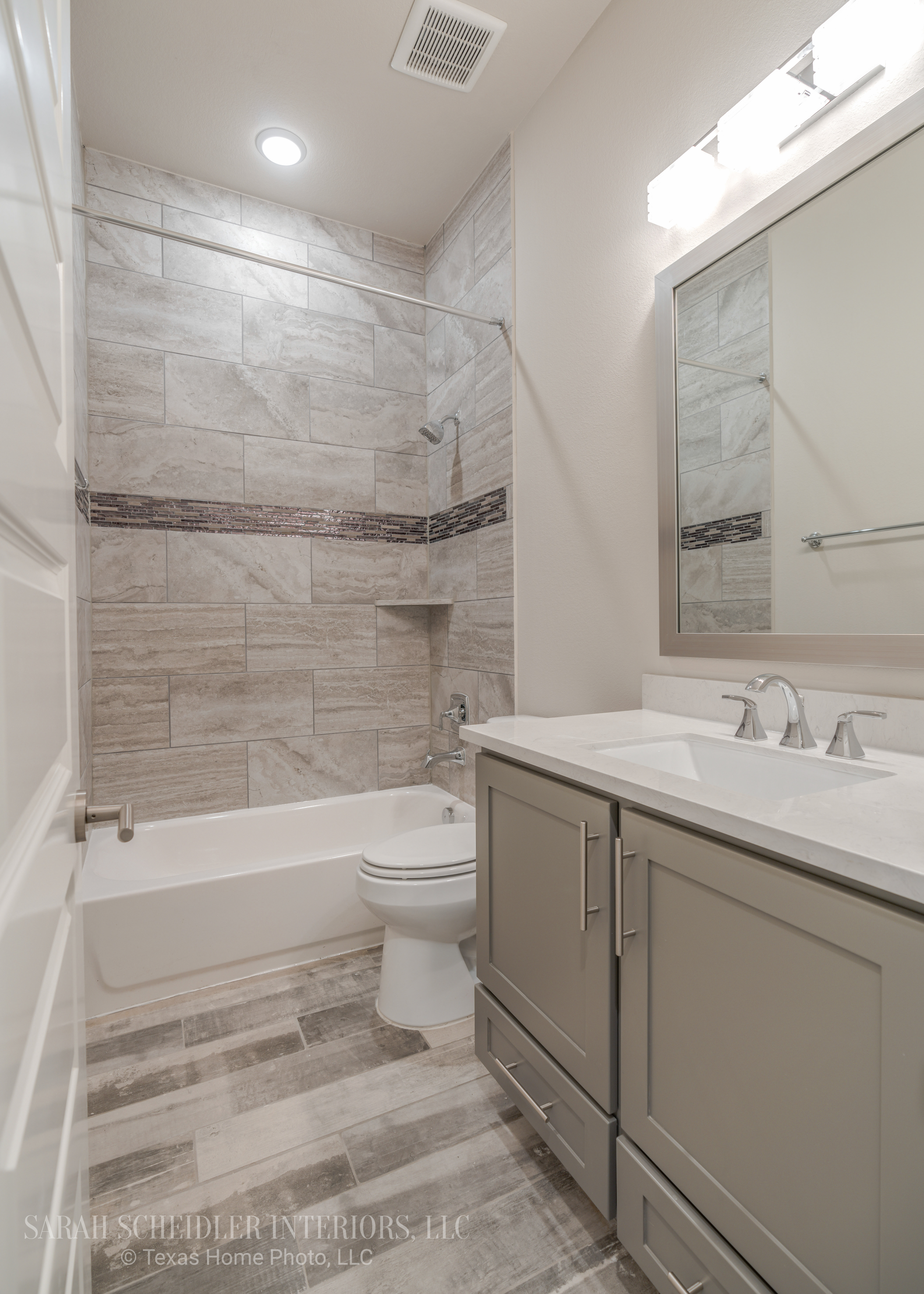 Grey Secondary Bathroom Design with Silestone Quartz Countertops, Chrome Accents, and Rustic Wood Tile Flooring