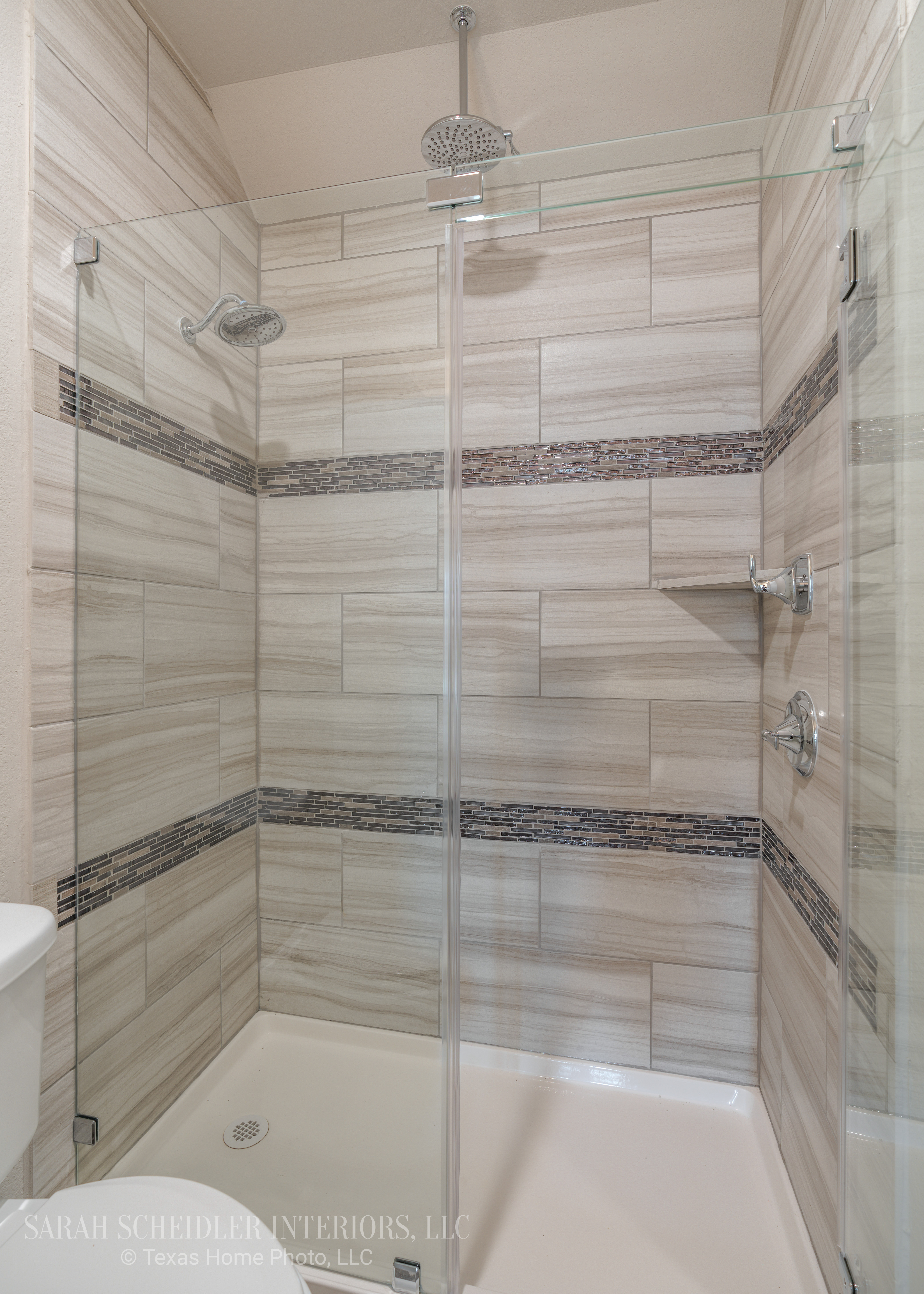 Secondary Bathroom Frameless Shower Design with Two Shower Heads, Glass Accent Tile, and Chrome Finishes