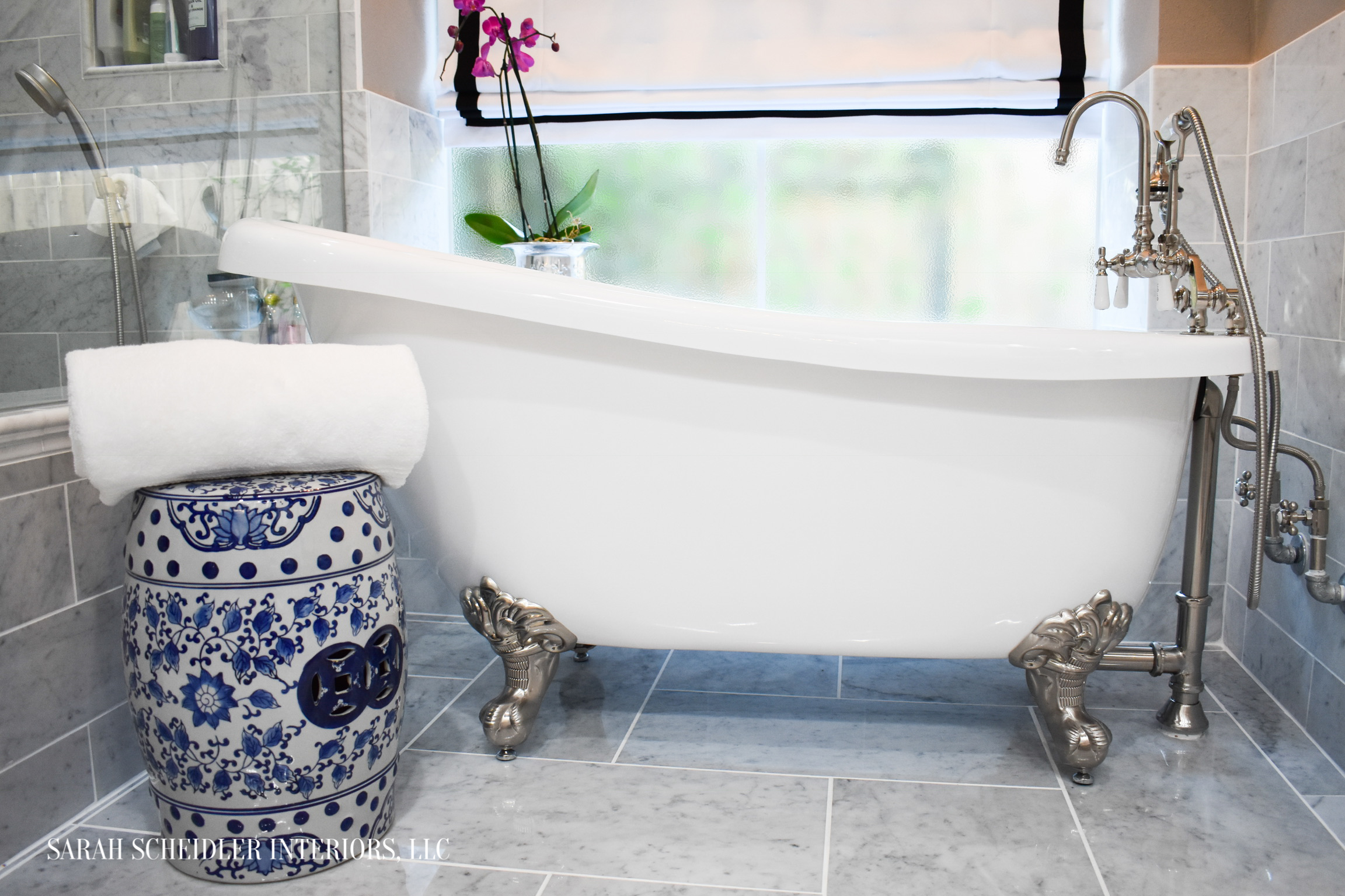 Clawfoot Tub in White and Grey Marble Primary Bathroom with Blue and White Decorative Accent Stool