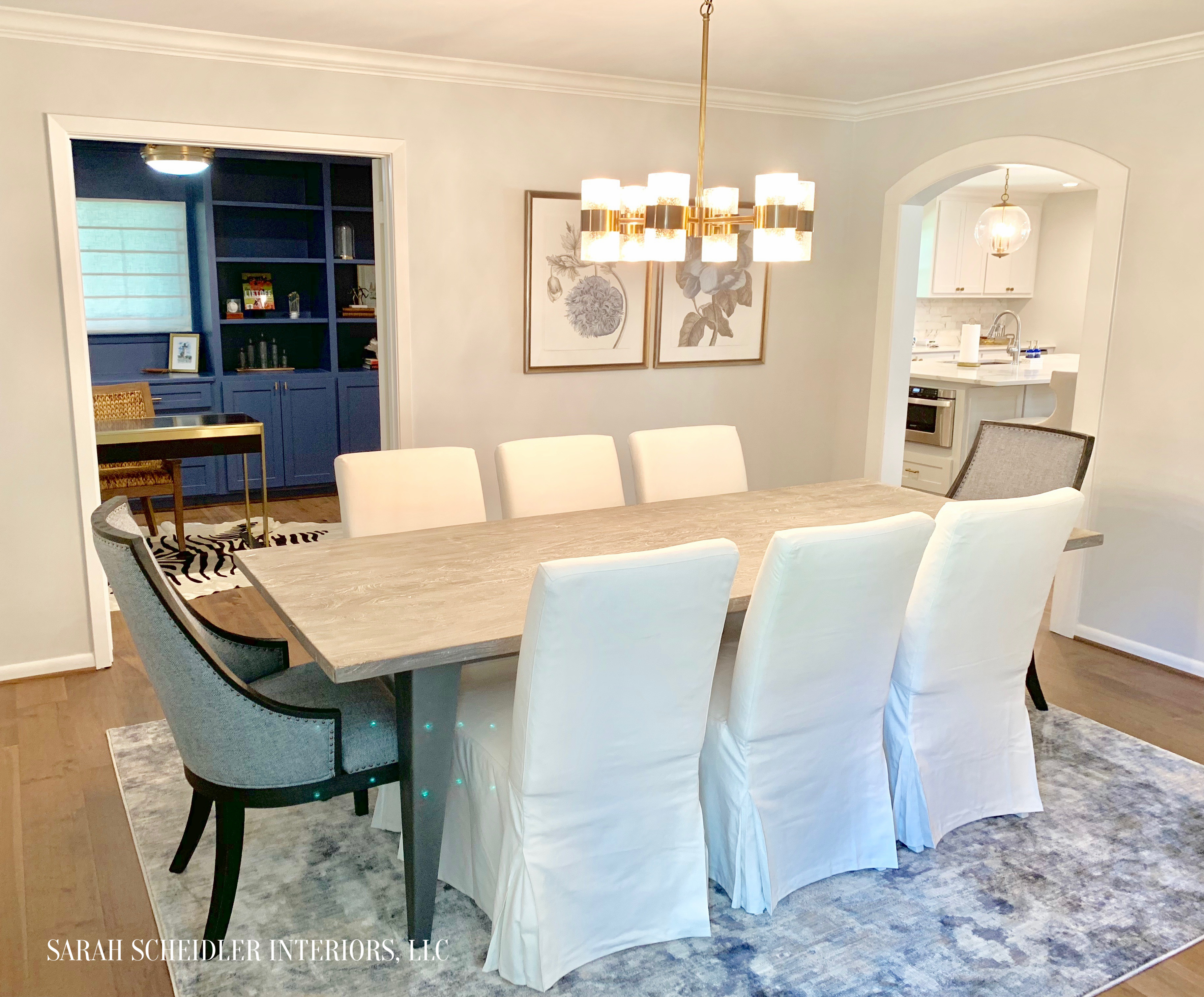 Dining Room Design with Blue Head Chairs, White Slip-Covered Dining Chairs, Botanical Art Prints, and Brass Lighting