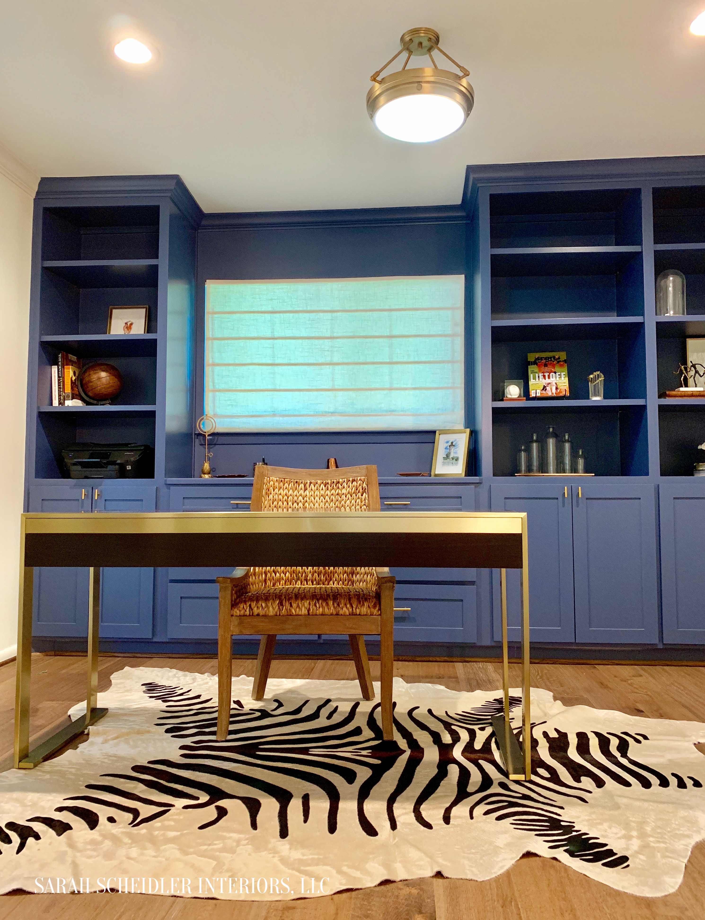 Blue and Brass Home Office with Built-Ins, Zebra Rug, Seagrass Chair and Modern Desk