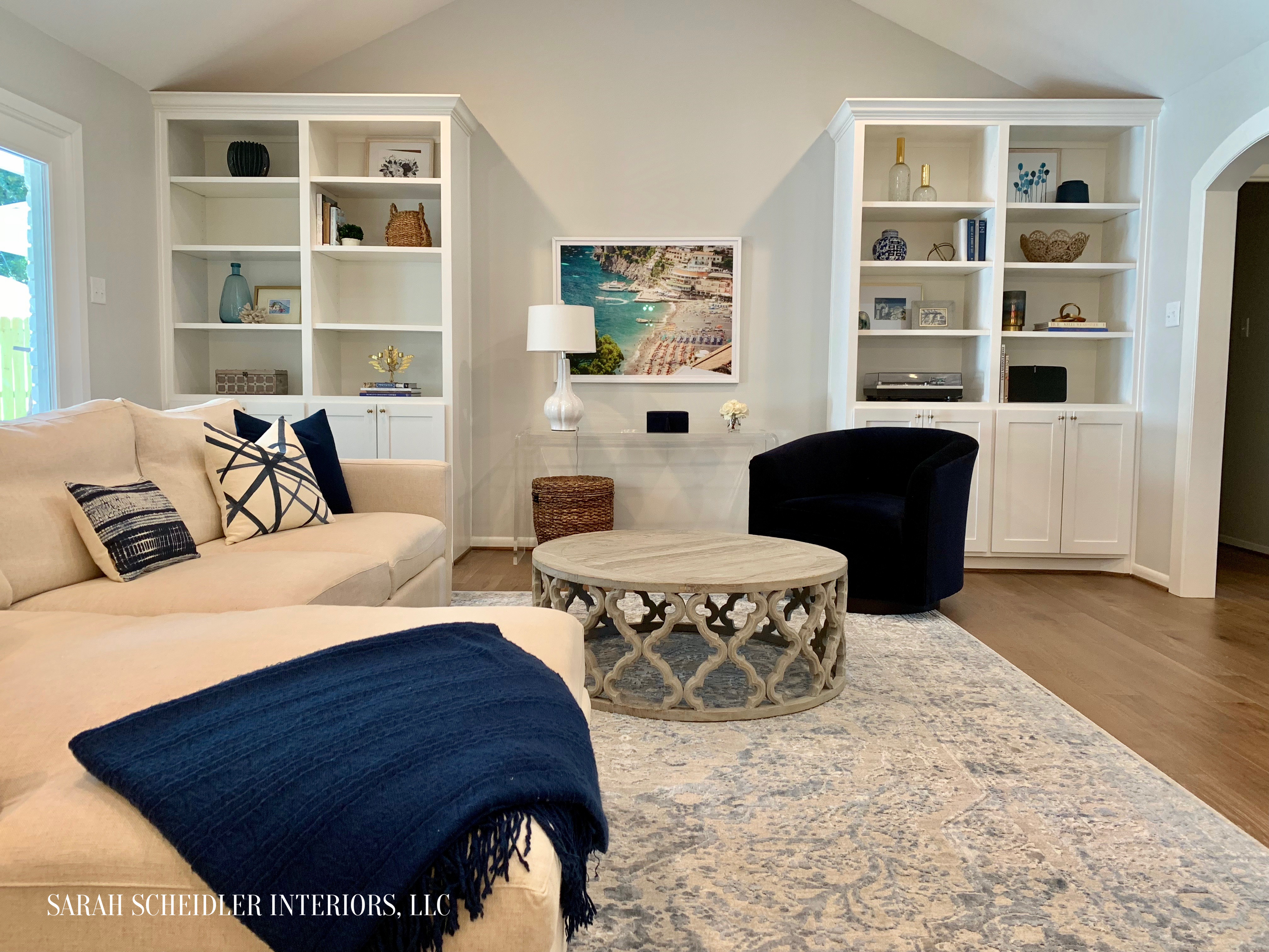 Coastal Cool Living Room Design with White Built-Ins, Blue Accents, Clear Acrylic Console Table, and Colorful Italian Art