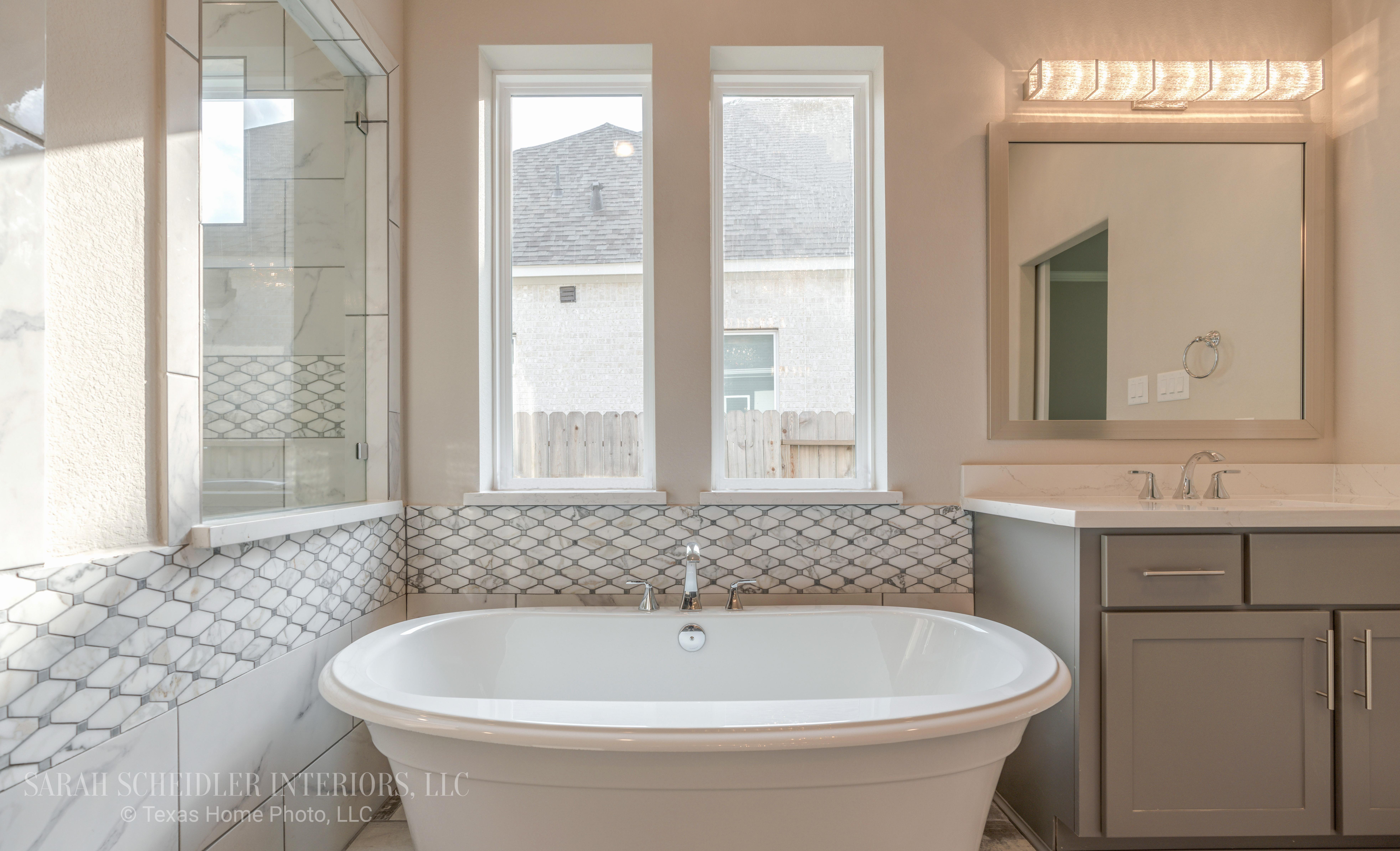White and Grey Master Bathroom with Freestanding Tub, Grey Cabinetry, Marble Wall Accent Tile, Wood Tile Flooring, Chrome Finishes, and Crystal Lighting