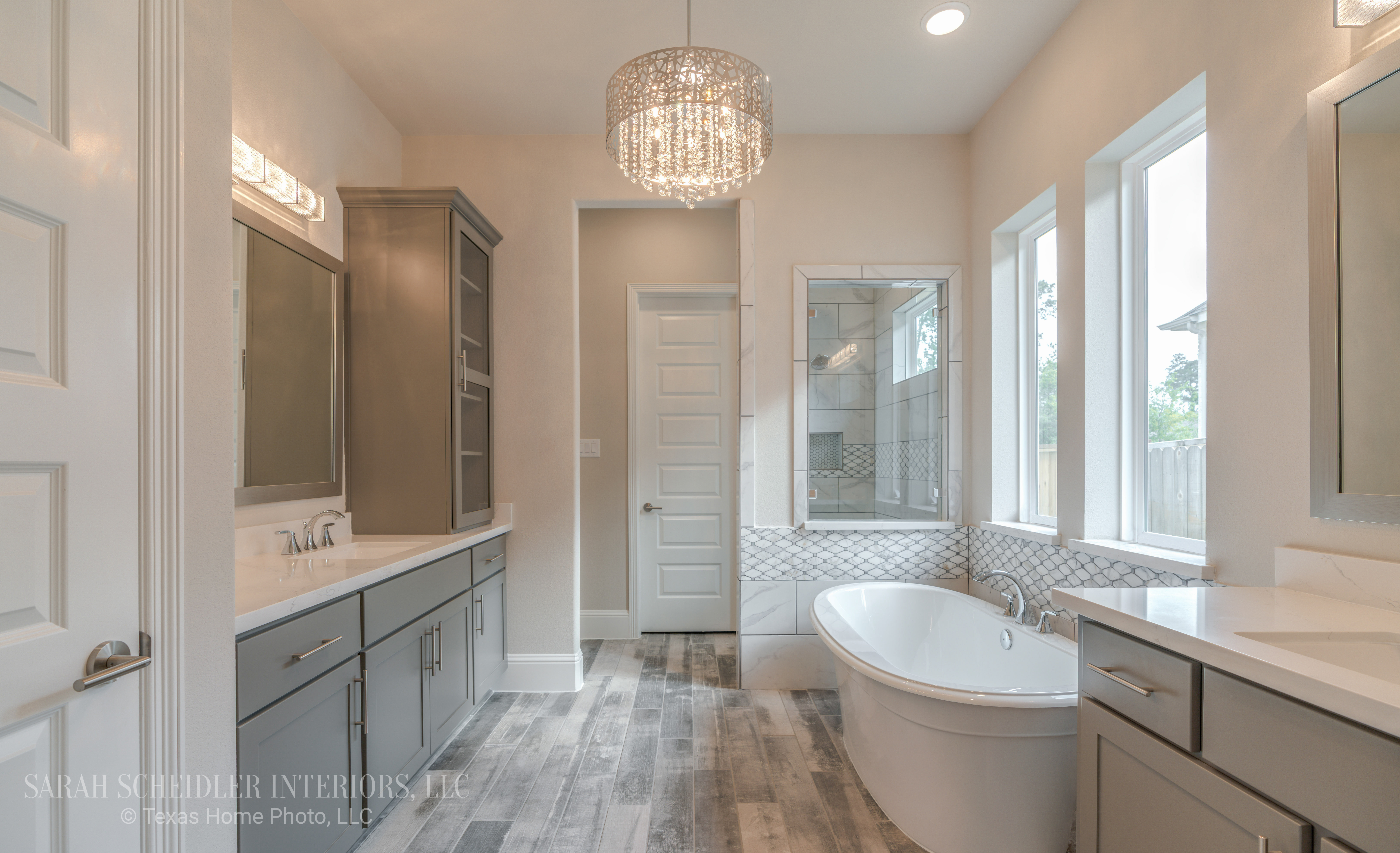 White and Grey Rustic Glam Master Bathroom Design with Freestanding Tub, Marble Accent Tile, Crystal Lighting and Wood Tile Flooring
