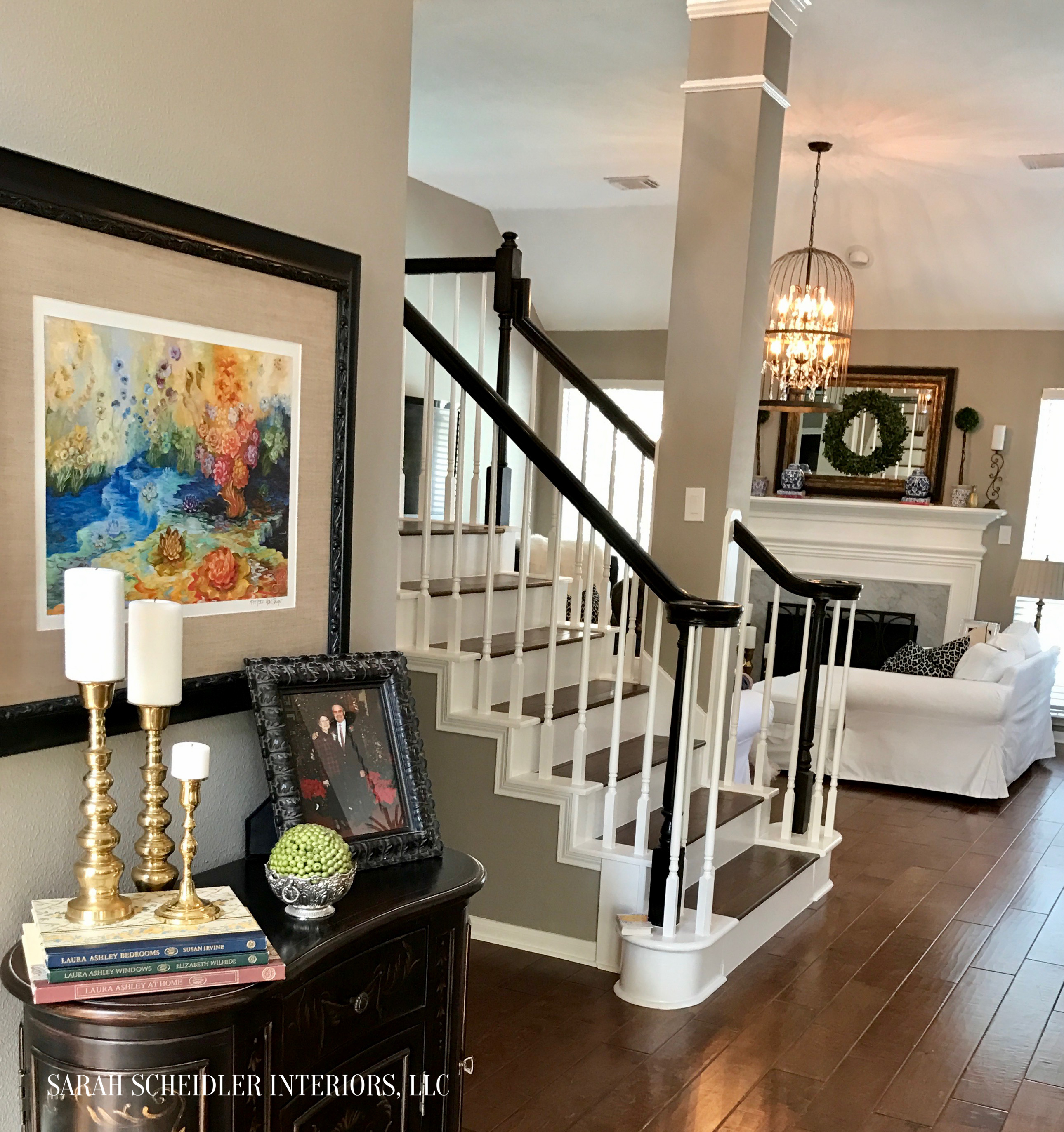 Open-Concept Entryway with Aged Brass Accents and Colorful Art Looking into White Living Room with Blue Accents and Birdcage Crystal Chandelier