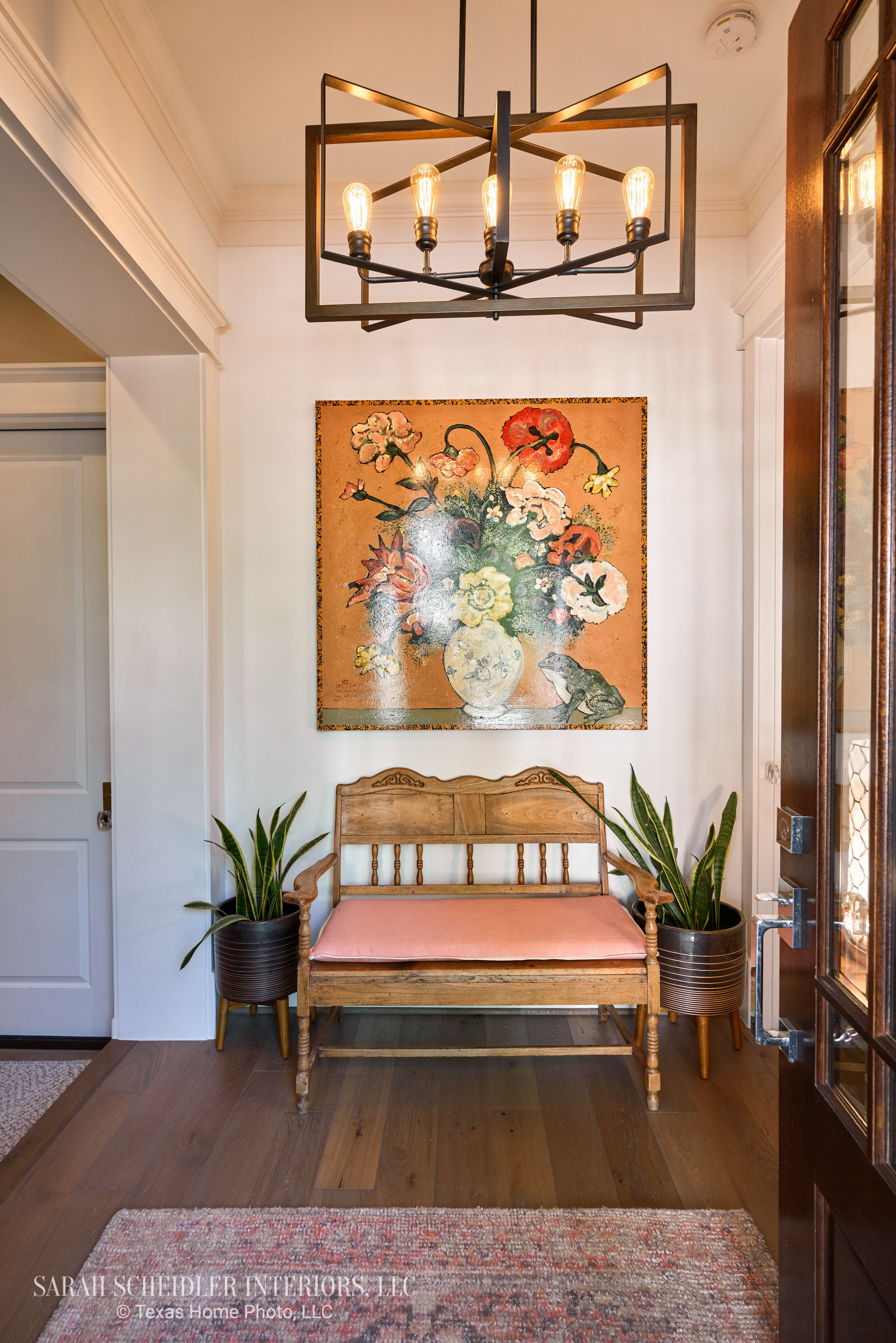 Entryway Design with Modern Light Fixture, Colorful Art, Antique Settee, and Potted Greenery