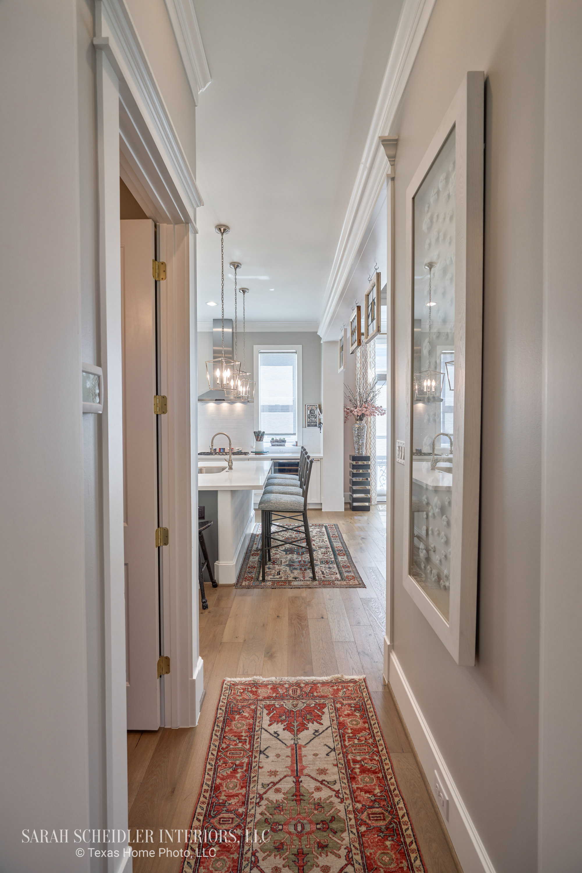 Hallway Design with Large-Scale Art Leading to White Open-Concept Kitchen
