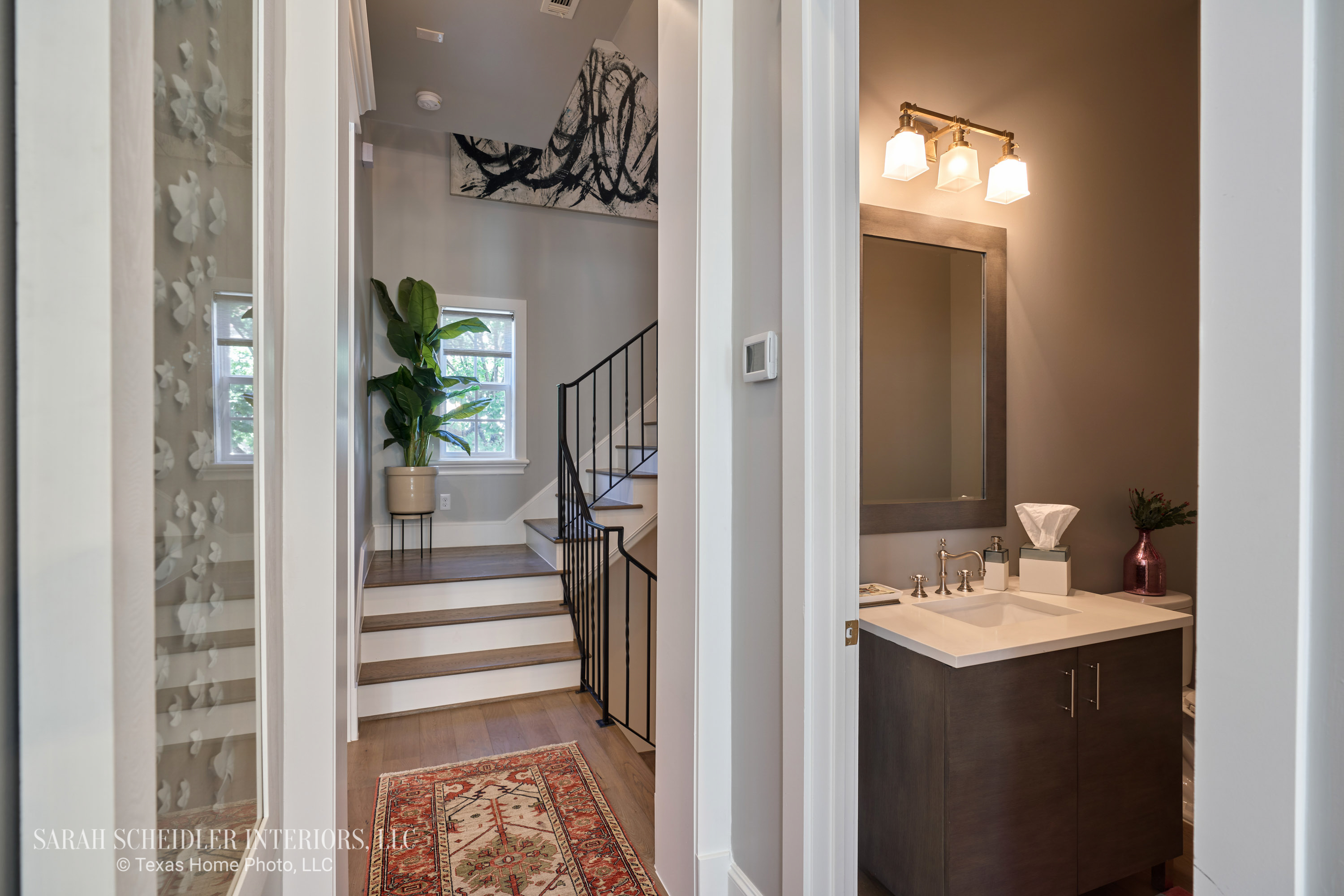 Hallway Design with Large-Scale Art, Colorful Rug Runner, and a Peak at the Powder Bathroom