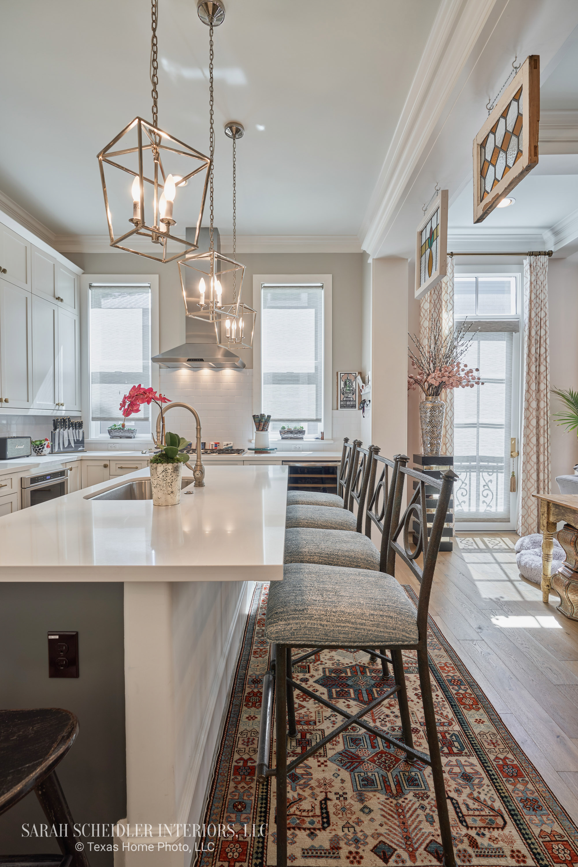 Open-Concept White Kitchen and Living Room Design with Pops of Color, Stained Glass Decorative Accents, Reupholstered Bar Stools, Sheer Custom Shades, Custom Living Room Drapes, and Faux Florals
